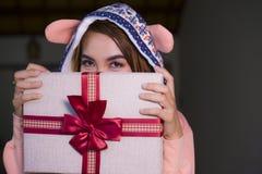 Mulher feliz e bonita nova no hoodie morno do inverno que guarda o Natal ou a caixa do presente de aniversário com a fita em suas fotos de stock