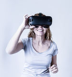 Mulher feliz e entusiasmado atrativa que usa os óculos de proteção 3d que olham a visão da realidade 360 virtual Imagem de Stock