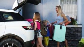 A mulher feliz e sua criança dois são bagagem da carga no carro video estoque