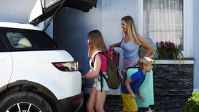 A mulher feliz e sua criança dois são bagagem da carga no carro vídeos de arquivo