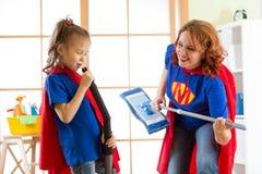 A mulher feliz e sua filha estão preparando-se para a limpeza da sala Mãe e sua menina da criança que jogam junto Família dentro fotos de stock royalty free
