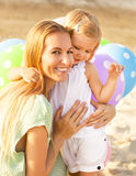 Mulher feliz e suas filhas pequenas com ballons fora Fotografia de Stock Royalty Free