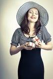 Mulher feliz elegante bonita que abre a caixa de presente vermelha e o sonho da curva Fotografia de Stock Royalty Free