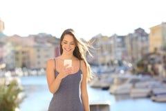 Mulher feliz em férias usando o telefone esperto fotos de stock royalty free