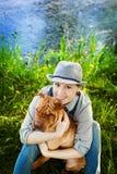 Mulher feliz em macacões e em chapéu da sarja de Nimes com seu cão Shar Pei que senta-se no prado perto do lago no por do sol Imagens de Stock Royalty Free