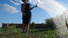 Mulher feliz em Panamá que molha um remendo do jardim de uma cabeça de chuveiro no slo-mo vídeos de arquivo