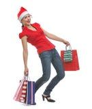 Mulher feliz em sacos de compra da terra arrendada do chapéu de Santa imagem de stock royalty free