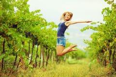 A mulher feliz em um vinhedo está saltando e está tendo o divertimento durante o h Imagem de Stock