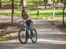 A mulher feliz está descansando com a bicicleta no parque foto de stock