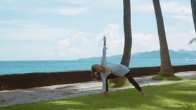 A mulher feliz está praticando a ioga, exercício do equilíbrio, pose do guerreiro, na praia do oceano com sons bonitos do fundo e vídeos de arquivo