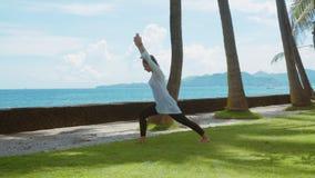 A mulher feliz está praticando a ioga, pose do guerreiro, exercício do equilíbrio, esticando, na praia, o fundo bonito, natureza  filme