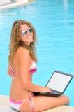 A mulher feliz está sentando-se perto da associação com portátil foto de stock royalty free