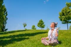 A mulher feliz est? sentando-se no gramado da grama A mulher bonita do estilo do boho com acess?rios aprecia o dia ensolarado do  imagens de stock