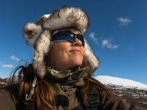Mulher feliz estar na paisagem do inverno, com o tampão do camo e os óculos de sol mornos imagens de stock