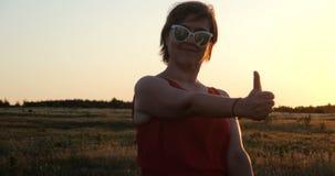 A mulher feliz exulta em um campo e em mostrar um polegar acima do gesto no slo-mo video estoque