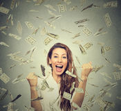A mulher feliz exulta os punhos de bombeamento ectáticos comemora o sucesso sob uma chuva do dinheiro