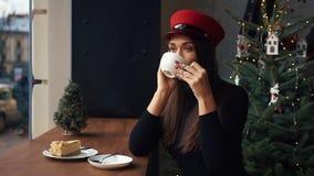 A mulher feliz fala no telefone que senta-se em um café confortável no dia de inverno frio video estoque
