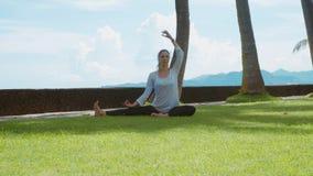 A mulher feliz faz a prática da ioga na pose dos lótus, o estiramento na praia do oceano na ilha Bali, o fundo bonito e os sons d vídeos de arquivo