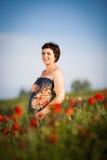 Mulher feliz grávida em um campo de florescência da papoila Imagens de Stock