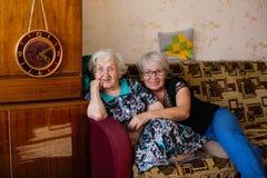 Mulher feliz idosa na casa com sua filha adulta que levanta para fotos foto de stock