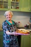 Mulher feliz idosa na cozinha com uma torta em suas mãos imagem de stock