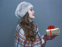 Mulher feliz isolada no fundo azul frio que dá a caixa atual Fotografia de Stock