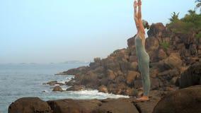 A mulher feliz levanta as mãos que fazem o movimento lento da prática da ioga video estoque