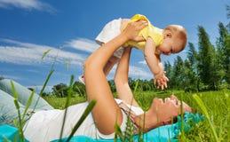 A mulher feliz levanta seu bebê acima com braços retos Fotografia de Stock