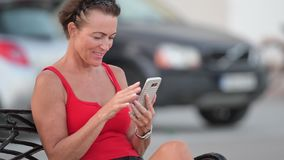 Mulher feliz madura do turista que usa o telefone ao sentar-se no banco video estoque