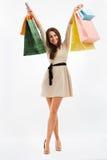 A mulher feliz mostra sacos de compras No branco fotografia de stock royalty free