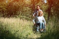 Mulher feliz na cadeira de rodas com seu marido outdoors foto de stock