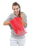 Mulher feliz na camiseta que retira algo do saco de compras Imagens de Stock