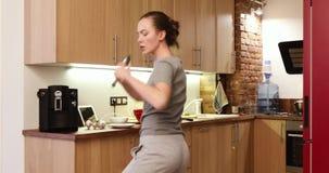 A mulher feliz na cozinha canta e dança