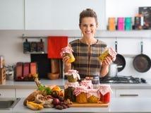 Mulher feliz na cozinha que guarda frascos de vegetais preservados Fotografia de Stock