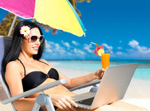 Mulher feliz na praia com um portátil Fotografia de Stock Royalty Free