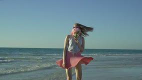 A mulher feliz na saia cor-de-rosa com óculos de sol está indo na praia aspira uma flor A menina bonita gerencie sobre a praia va filme