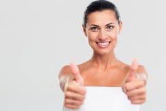 Mulher feliz na toalha que mostra o polegar acima do sinal imagens de stock