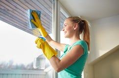 Mulher feliz nas luvas que limpam a janela com o pano Fotografia de Stock Royalty Free