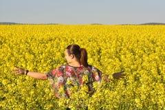 Mulher feliz no campo de florescência da colza na mola Foto de Stock Royalty Free