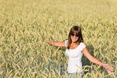 A mulher feliz no campo de milho aprecia o por do sol fotografia de stock royalty free