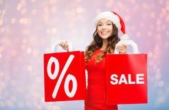 Mulher feliz no chapéu de Santa com sacos de compras Fotos de Stock