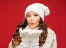 A mulher feliz no inverno veste o sopro nas palmas imagem de stock