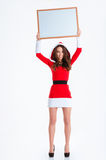 Mulher feliz no pano de Papai Noel que guarda a placa vazia Fotos de Stock Royalty Free