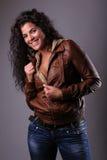 Mulher feliz no revestimento de couro e nas calças de brim Imagens de Stock
