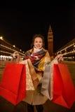 Mulher feliz no revestimento do inverno que mostra sacos de compras quando em Veneza Imagem de Stock