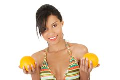 Mulher feliz no roupa de banho que guarda laranjas Foto de Stock