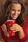 Mulher feliz no vestido vermelho que tem o copo da bebida quente fotografia de stock royalty free