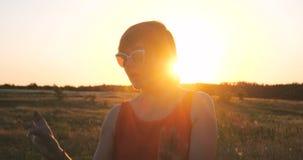 Mulher feliz nos óculos de sol que dançam em um campo no por do sol no verão video estoque