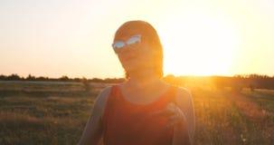 Mulher feliz nos óculos de sol que dançam em um campo no por do sol no verão imagens de stock royalty free