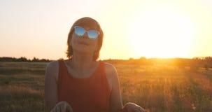 Mulher feliz nos óculos de sol que dançam em um campo no por do sol no verão foto de stock